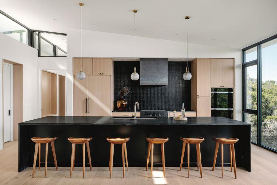 Большой черный остров, отделяющий кухню от остальных общественных зон, служит элегантной барной стойкой.