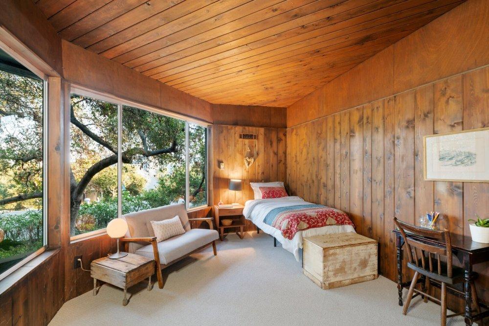 Этот большой дровяной камин создает ощущение уюта в гостиной открытой планировки.