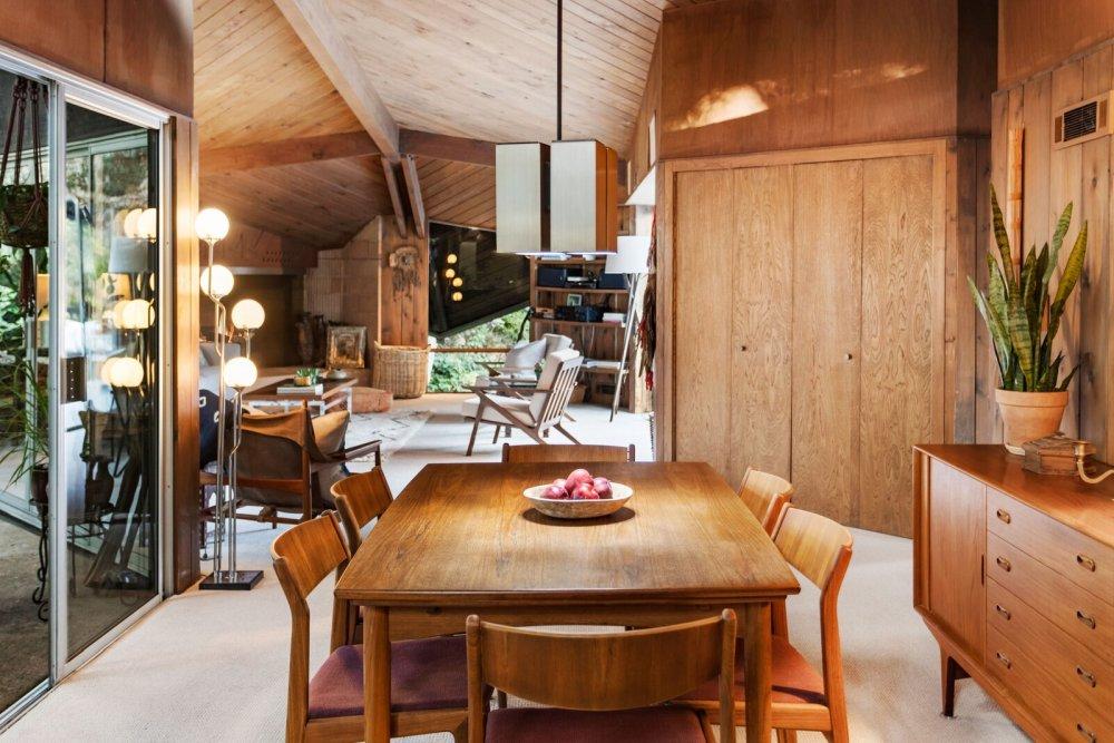 Небольшая обеденная зона выступает в роли разделителя между гостиной и кухней.