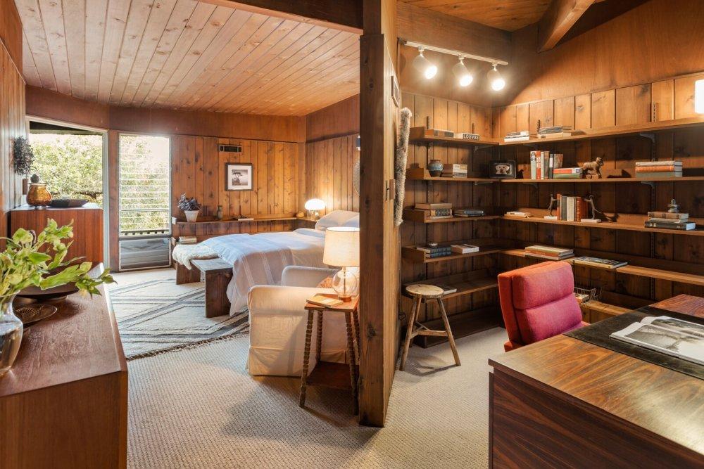 В главной спальне есть отдельный небольшой рабочий уголок с террасой и множеством открытых полок.