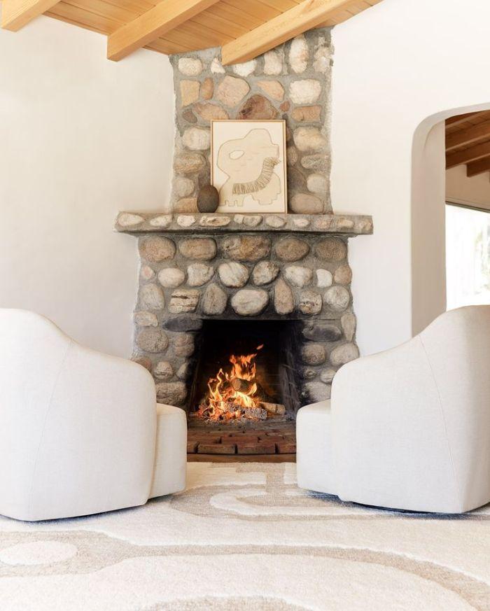 Каменный камин с двумя белыми креслами