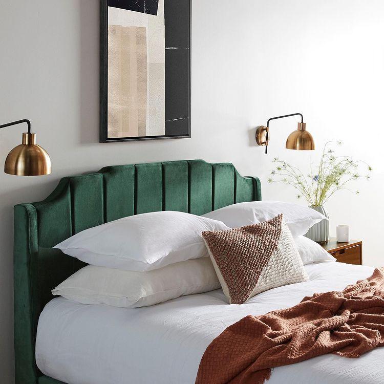 зеленая кровать и золотые лампы на стене