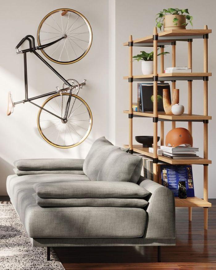 комната с серым диваном и велосипедом на стене